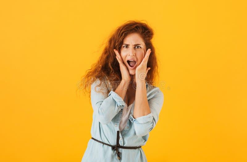 尖叫兴奋的情感的妇女20s握手在面孔和 免版税图库摄影