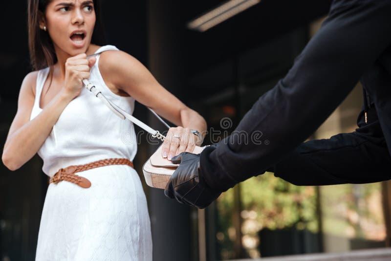 尖叫和战斗与强盗whi的妇女窃取她的袋子 免版税库存照片
