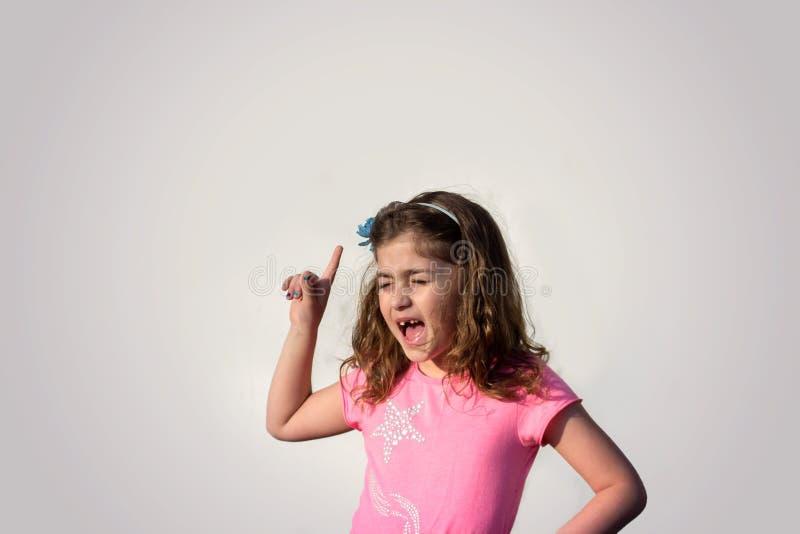 尖叫和指向她的手指的女孩反对灰色背景 免版税库存图片
