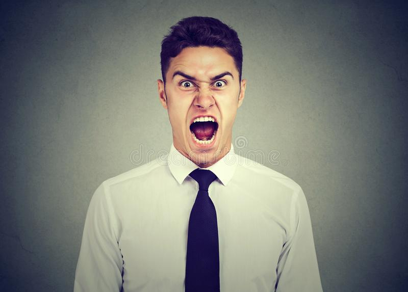尖叫年轻恼怒的商人 库存图片