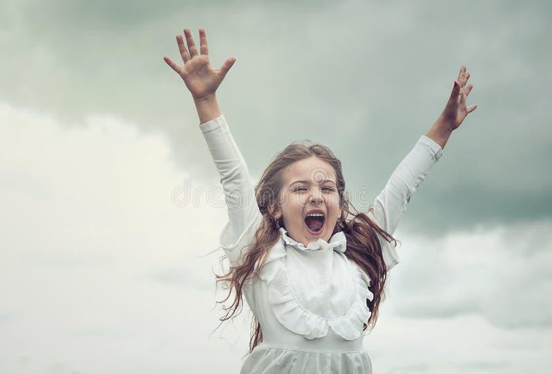 尖叫激动的逗人喜爱的女孩举胳膊和,幸福概念 库存图片