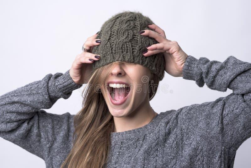 尖叫的年轻女人画象有盖她的眼睛的被编织的盖帽的 免版税库存图片
