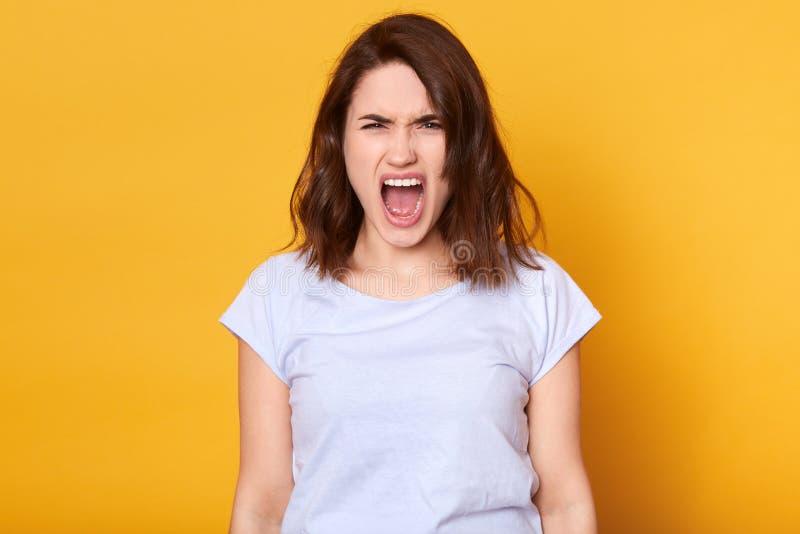尖叫的情感恼怒的妇女被隔绝在黄色演播室背景 半身画象年轻深色女性佩带 库存图片
