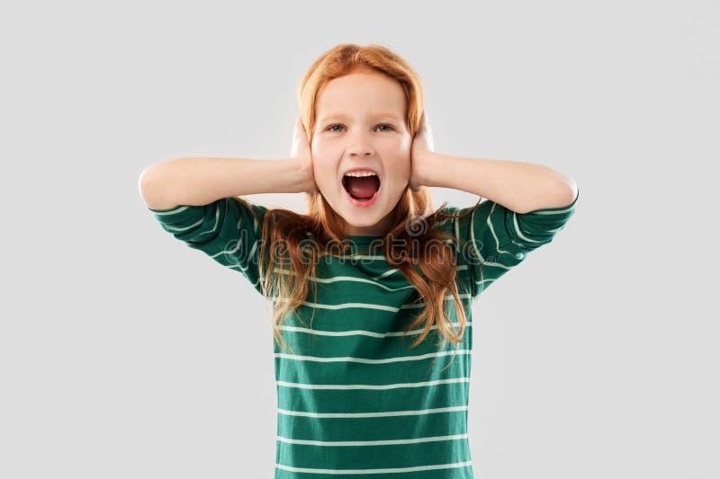 尖叫的红发女孩关闭的耳朵用人工 库存图片