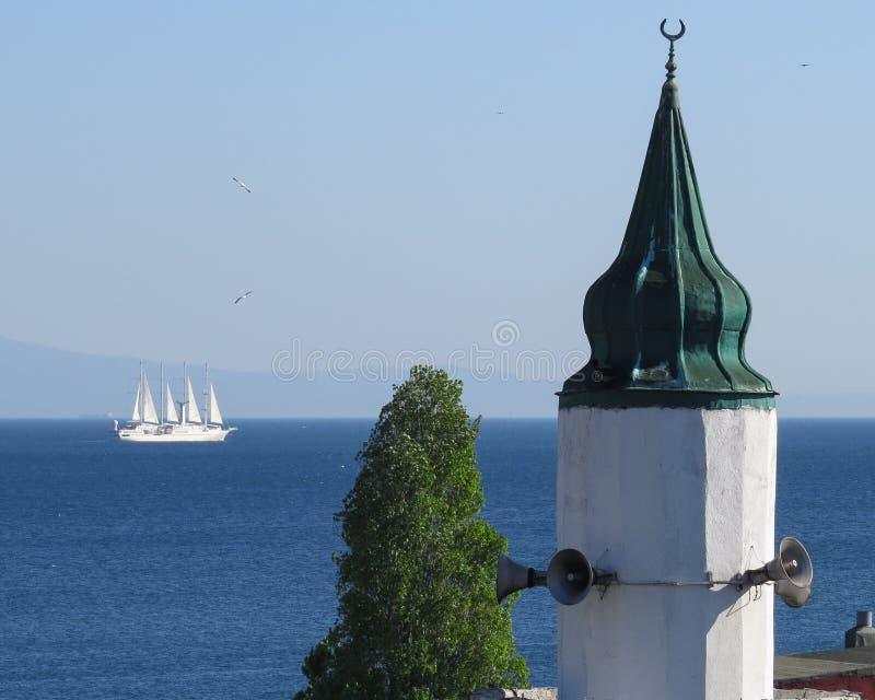 尖塔的上面和植物反对海背景,天空和白色风船航行过去 库存图片