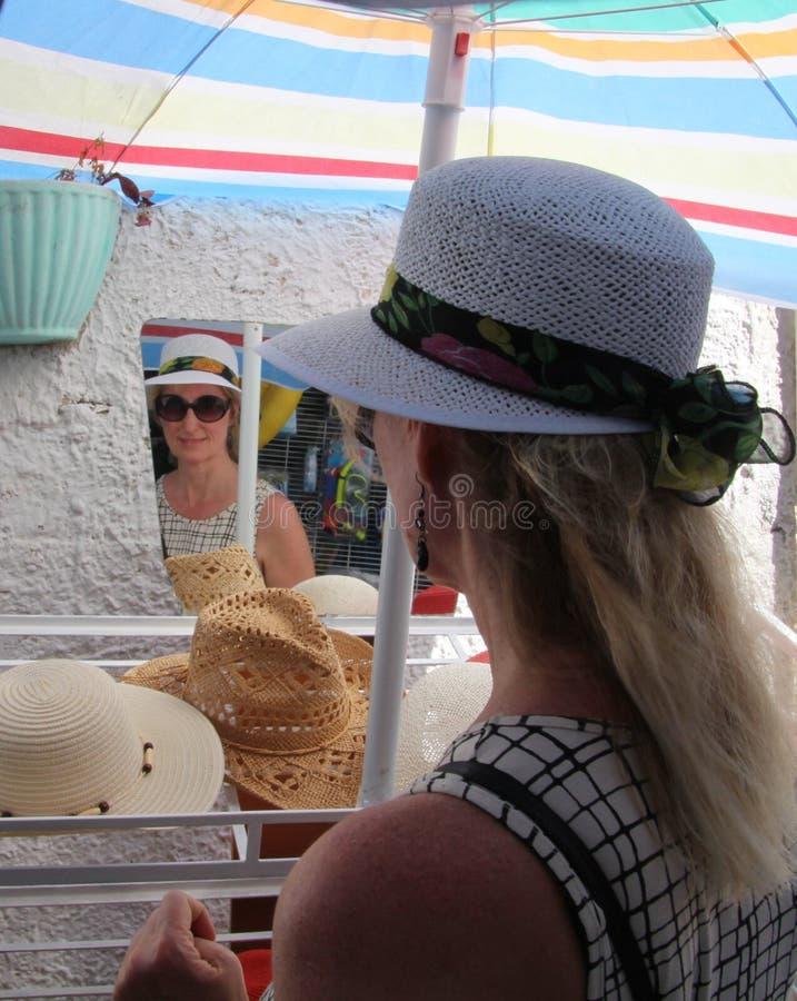 尝试一个新的帽子和太阳镜的妇女 库存图片