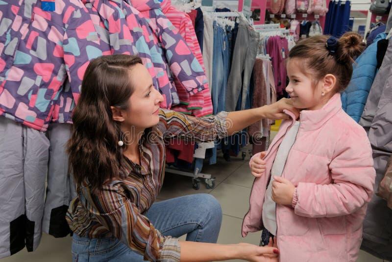 尝试在一件夹克的女孩为在儿童的服装店的冬天 愉快的年轻母亲和女儿购物 库存图片