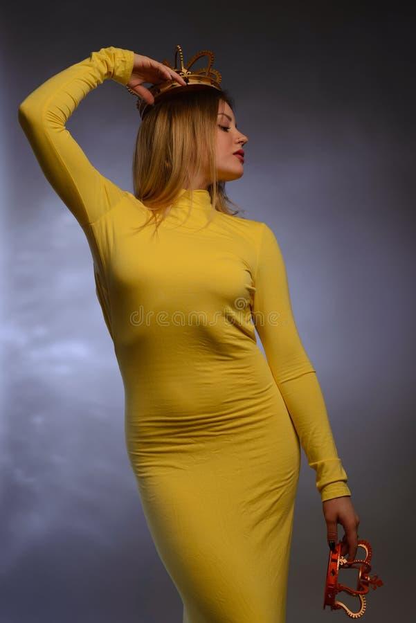 尝试在冠的黄色晚礼服的美丽的女孩 免版税库存照片