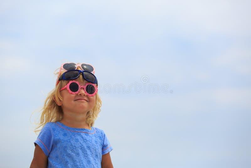 尝试在太阳镜的逗人喜爱的小女孩在天空 库存图片