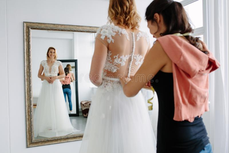 尝试在婚礼礼服的新娘在商店 免版税库存图片