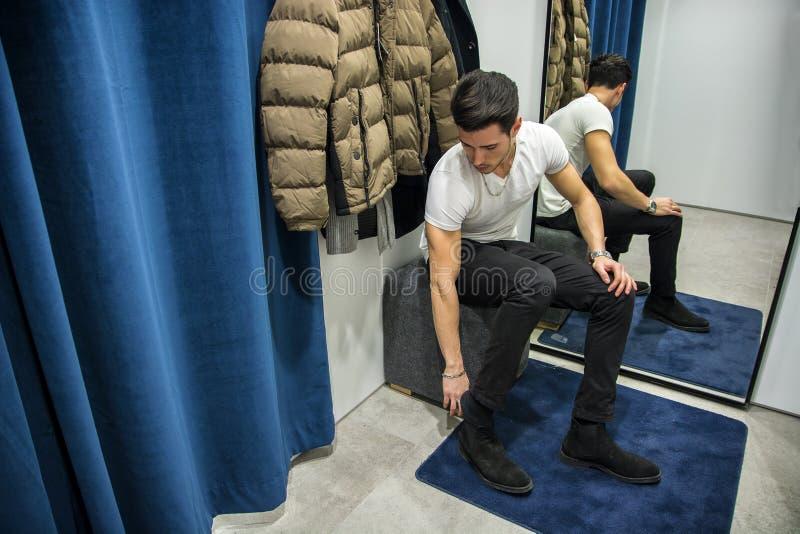 尝试在服装店的衣裳的年轻人 免版税库存图片