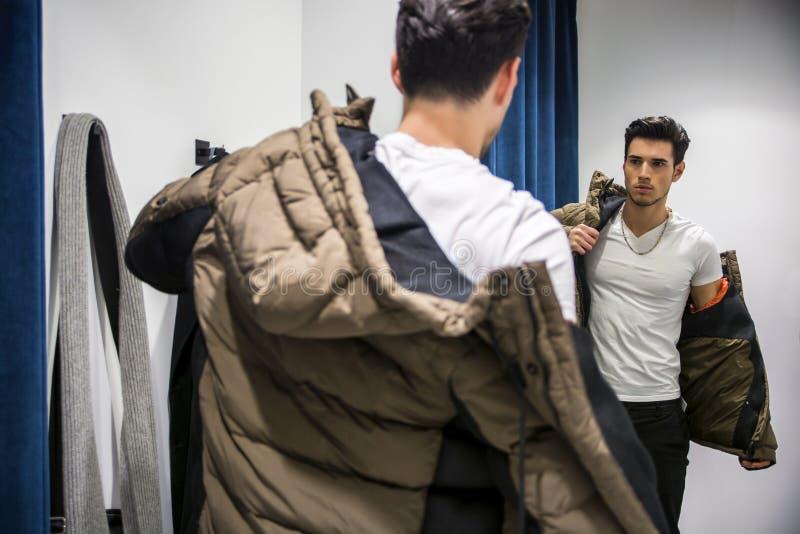 尝试在服装店的衣裳的年轻人 免版税库存照片