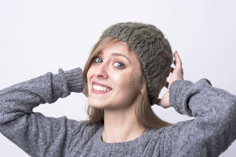 尝试在灰色被编织的童帽盖帽的逗人喜爱的迷人的年轻女人微笑对照相机 库存图片