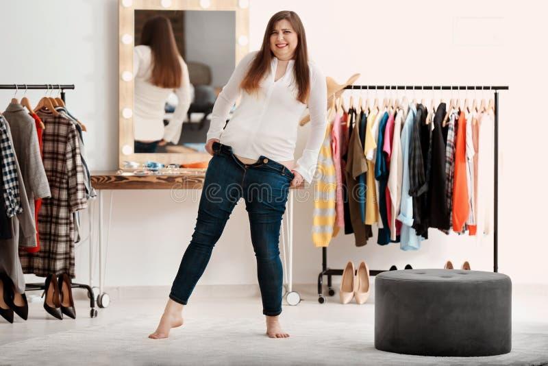 尝试在牛仔裤的美丽的超重妇女 图库摄影