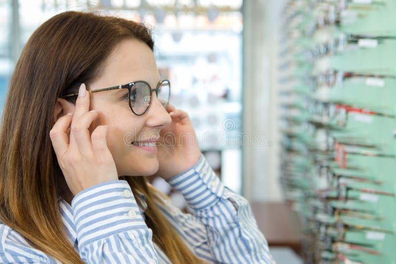 尝试在玻璃的妇女在光学商店 免版税库存图片