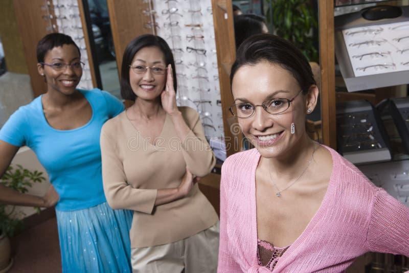 尝试在眼镜的多种族朋友在验光师 图库摄影