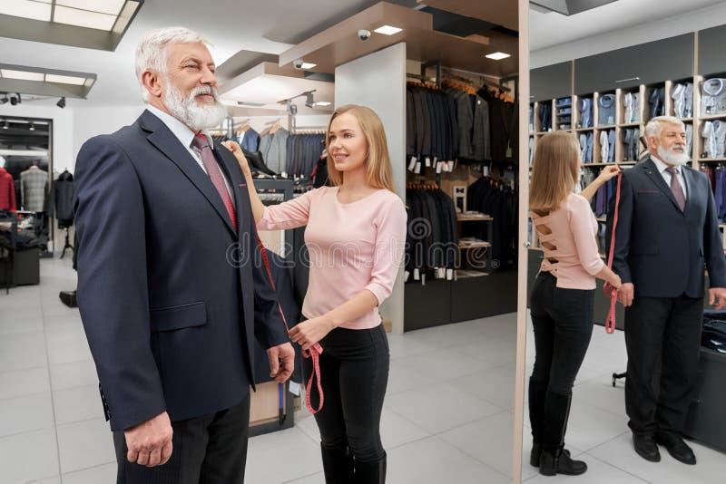 尝试在精品店的新的正装的典雅的更老的人 免版税库存照片