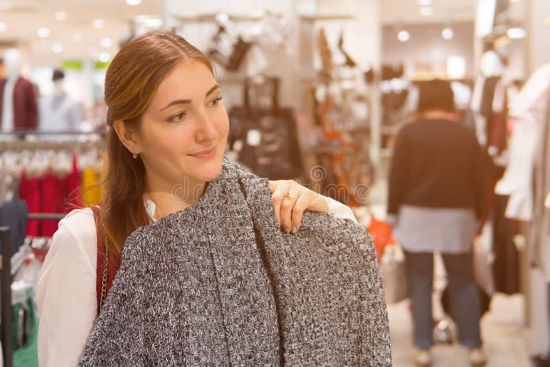 尝试在羊毛夹克的妇女在衣物商店 免版税库存照片