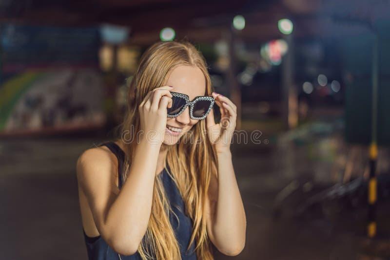 尝试在走的街道亚洲市场上的玻璃的年轻女人游人 免版税库存图片