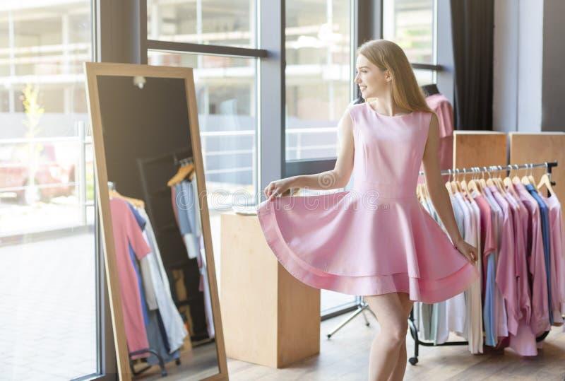 尝试在镜子前面的俏丽的年轻女人桃红色礼服 库存照片