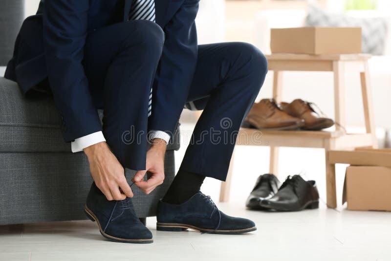 尝试在鞋子的年轻人 免版税库存照片