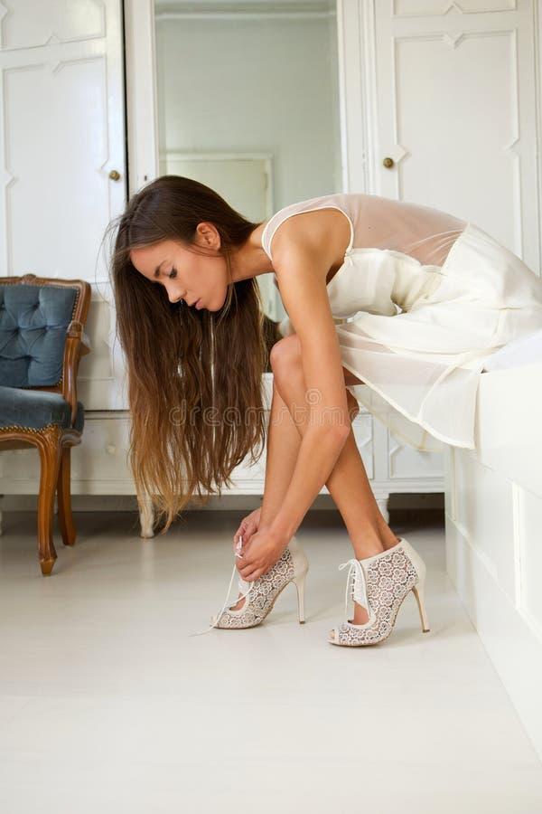 尝试在鞋子的美丽的少妇 免版税库存照片