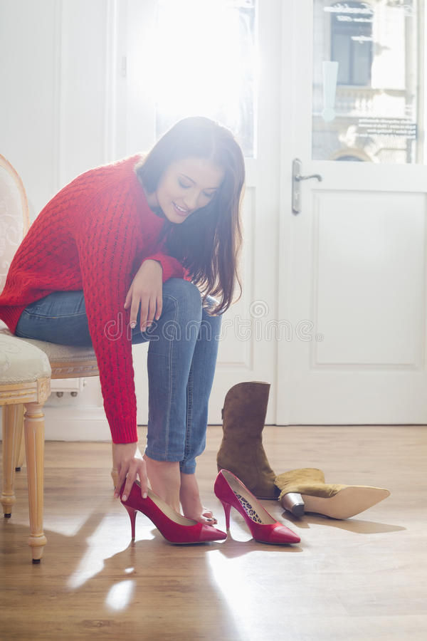 尝试在鞋类的妇女在商店 免版税库存照片