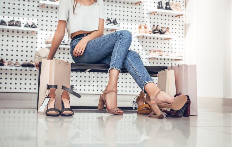 尝试在高跟鞋鞋子的美丽的少妇,当坐沙发在鞋店时 免版税图库摄影