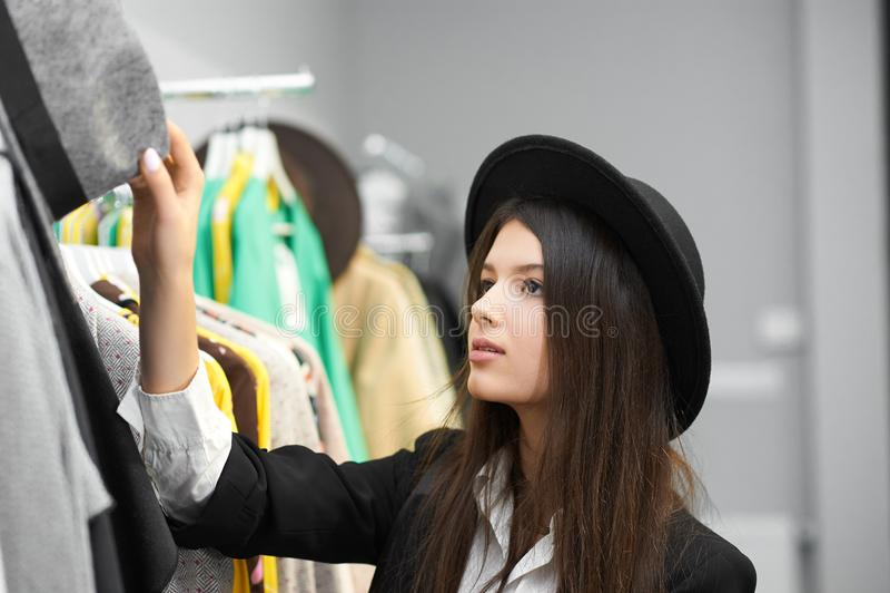 尝试在黑帽会议的俏丽的女孩在衣物商店 免版税库存图片