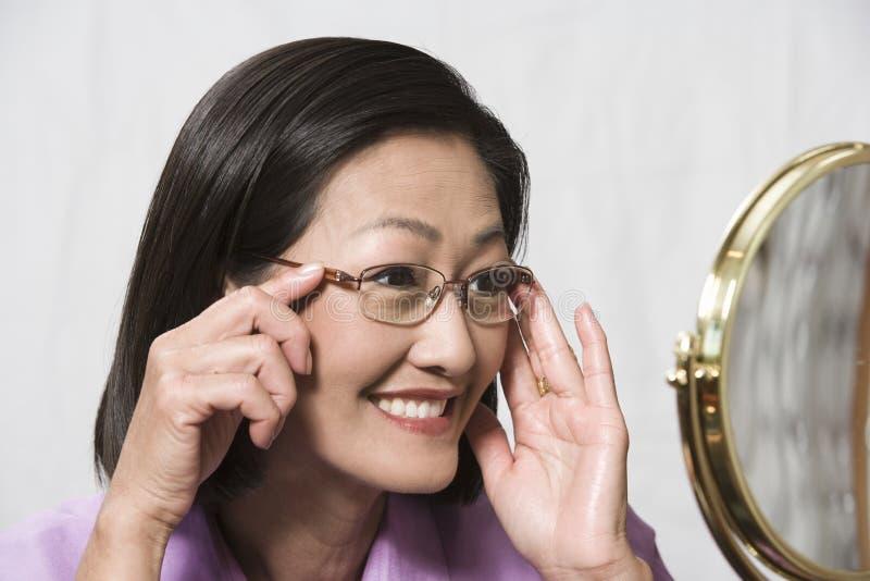 尝试在玻璃和看镜子的妇女 免版税库存图片