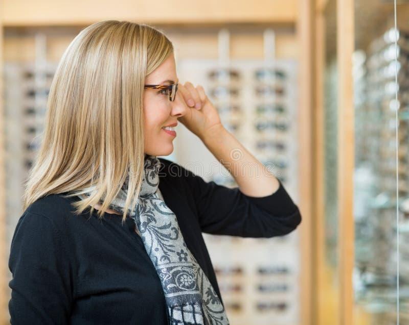 尝试在玻璃的妇女在眼镜师商店 免版税库存照片