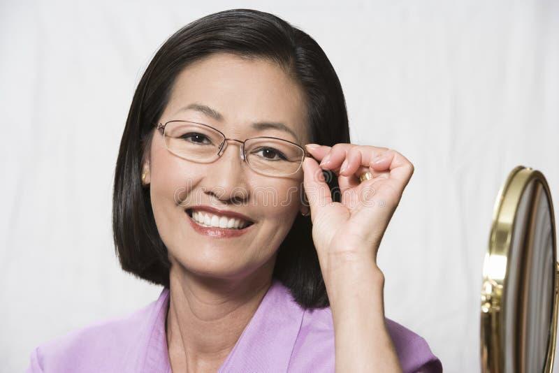尝试在玻璃的成熟中国妇女 库存照片