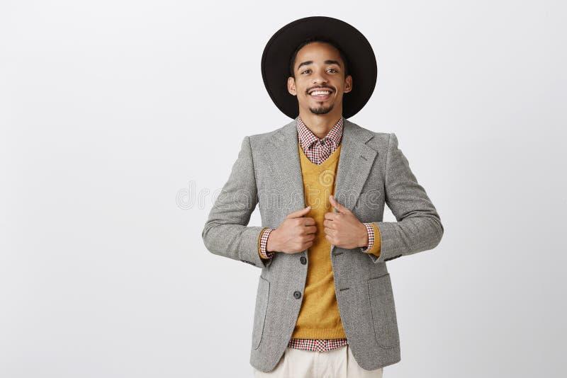 尝试新式,购买时髦夹克在商店 愉快的成功的深色皮肤的有胡子的人画象黑帽会议的 免版税库存照片