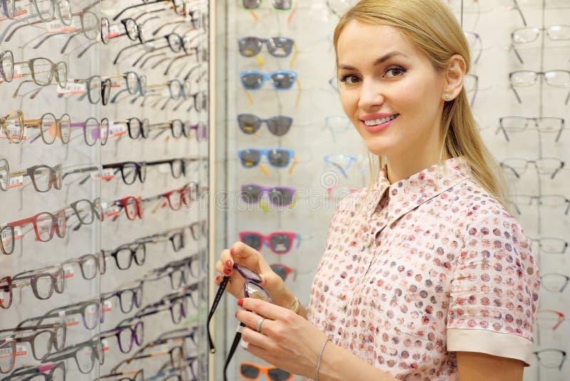 尝试新的玻璃的微笑的年轻女人在眼镜师商店 免版税库存图片