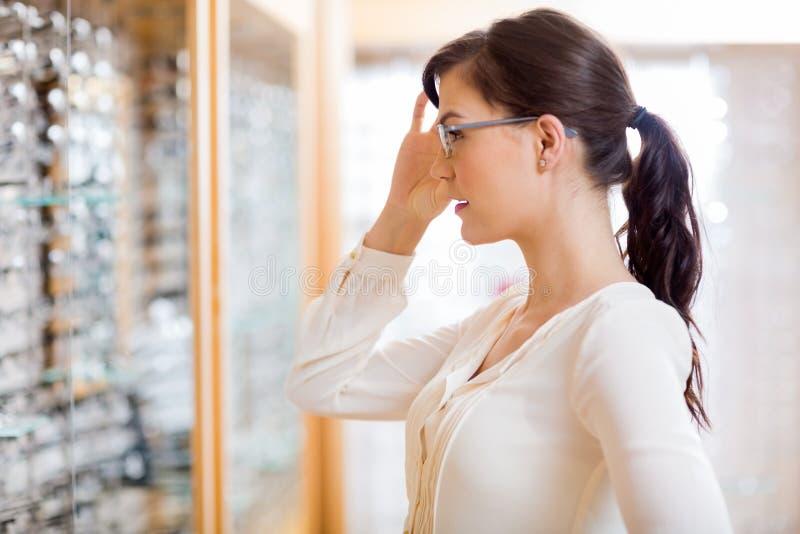 尝试新的玻璃的妇女在眼镜师商店 免版税库存照片