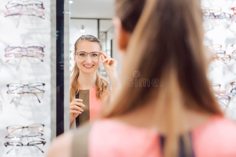 尝试时兴的玻璃的少妇在验光师商店 免版税库存图片