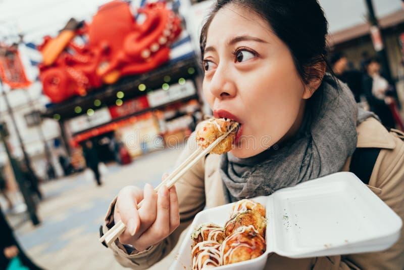 尝试鲜美著名takoyaki的夫人游人 免版税库存照片