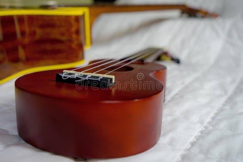 尤克里里琴串持有人或木尤克里里琴在床上,反对声学吉他背景 图库摄影
