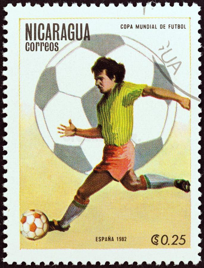尼加拉瓜-大约1982年:在尼加拉瓜打印的邮票显示跑与球的球员,大约1982年 免版税图库摄影