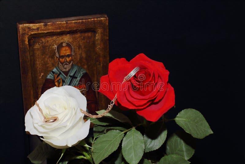 尼古拉斯Wonderworker,在红色和白色玫瑰的结婚戒指象在黑背景 符号概念—家庭,爱, 免版税图库摄影