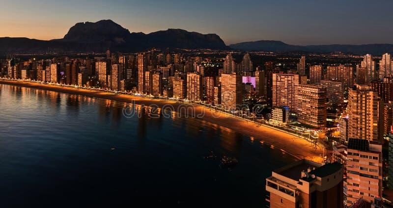 贝尼多姆市的有启发性摩天大楼在晚上 西班牙 免版税库存图片