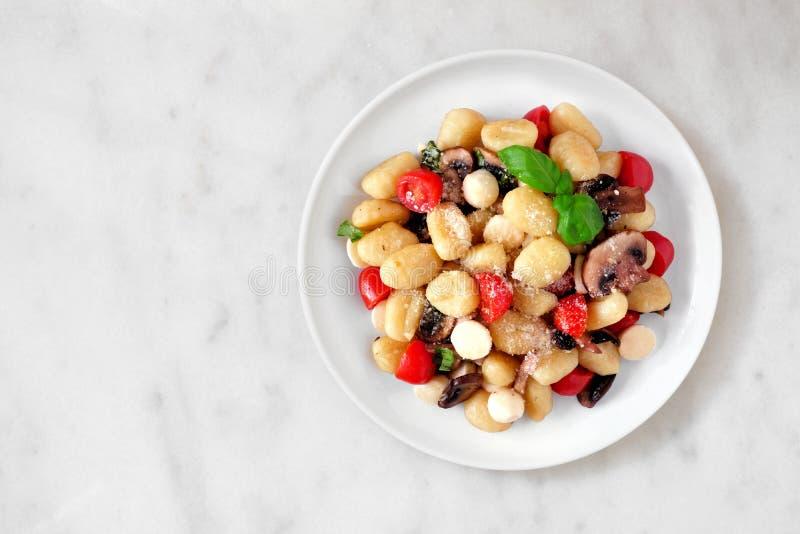 尼奥基用蕃茄、无盐干酪、蘑菇和蓬蒿,在白色大理石的顶视图 免版税库存照片