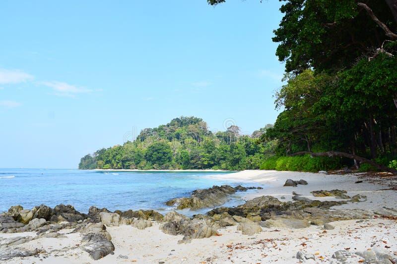 尼尔在Radhanagar海滩、Havelock海岛、安达曼&尼科巴,印度-天蓝色的水、蓝天、石头和绿叶的` s小海湾 库存图片