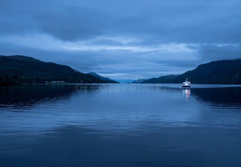 尼斯湖,苏格兰的高原中心 在水的小船在微明 拍摄从堡垒奥古斯都 免版税库存图片