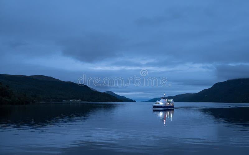尼斯湖,苏格兰的高原中心 在水的小船在微明 拍摄从堡垒奥古斯都 库存图片