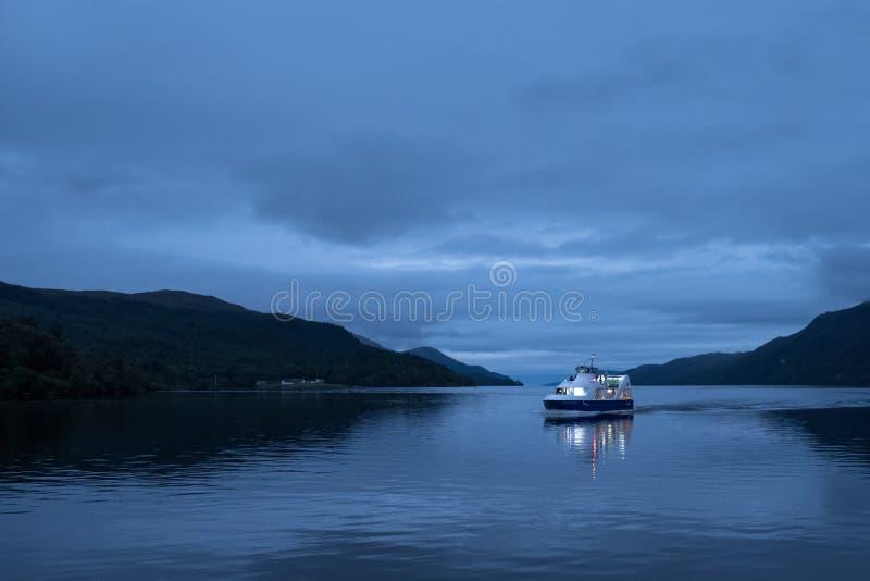 尼斯湖,苏格兰的高原中心 在水的小船在微明 拍摄从堡垒奥古斯都 库存照片