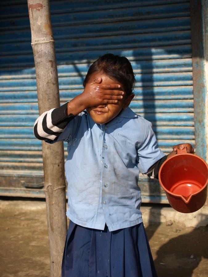 尼泊尔女孩洗涤的表面 库存图片