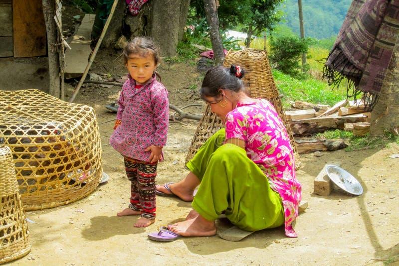 尼泊尔小女孩和她的母亲在村庄 免版税库存图片