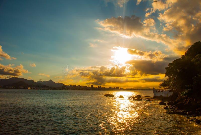 尼泰罗伊,巴西:日落的古老堡垒在城市尼泰罗伊 美好的风景有山和海视图 图库摄影