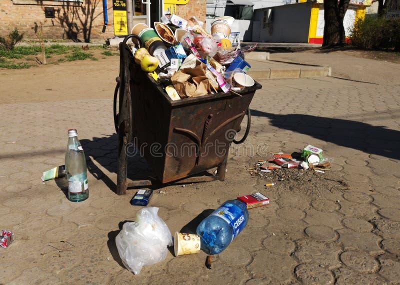 尼科波尔,乌克兰,2019年5月20日:在乌克兰街道上的一个拥挤垃圾箱,有在铺路板的垃圾的 库存图片